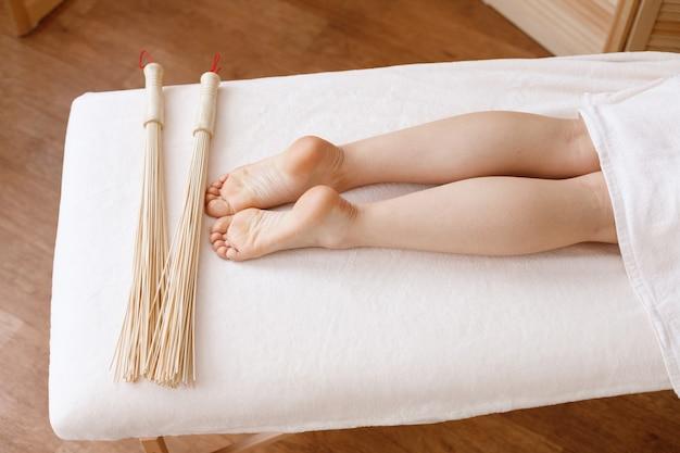 Piedi e bastoni sul lettino da massaggio