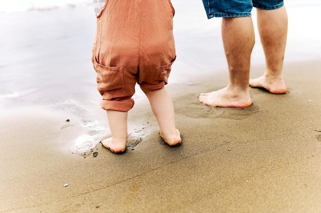 Piedi di un bambino di tre anni accanto a suo padre in riva al mare