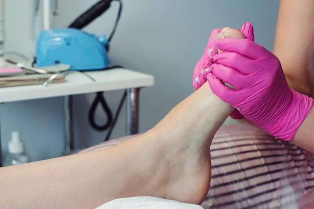 Trattamento piedi. trattamento di bellezza per le gambe. maestro di pedicure che massaggia i piedi con lo scrub. pedicure professionale nel salone di bellezza. donna che si rilassa al salone, che si prende cura delle unghie.