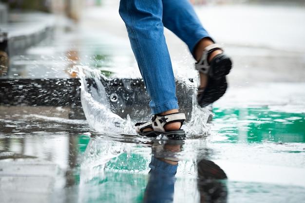 Piedi di donna che corre in pozzanghere con spruzzi d'acqua nel giorno di pioggia