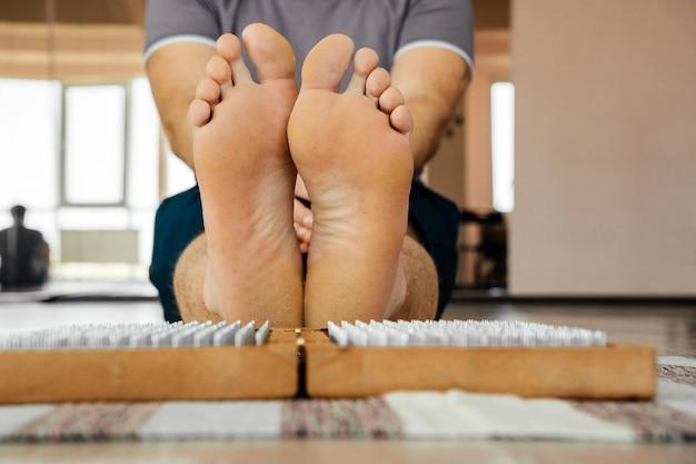 Piedi e tavola di legno con chiodi di metallo affilati. pedana sadhu. formazione pratica di rilassamento yoga