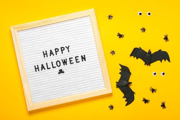 Lavagna in feltro con testo, citazione, pipistrello nero, ragni. vista dall'alto piatto lay happy halloween
