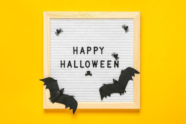 Lavagna in feltro con testo, citazione, pipistrello nero, ragni. vista dall'alto piatto laici felice