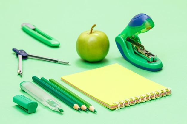 Pennarello, matite colorate, un quaderno, un compasso, un tagliacarte, una mela e una cucitrice su sfondo verde. torna al concetto di scuola. materiale scolastico. profondità di campo.