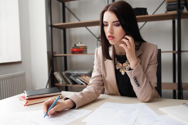 Ragioniere femminile che controlla i documenti finanziari