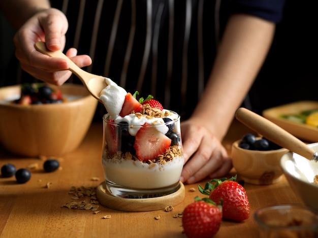 Femmina aggiungendo yogurt greco sul bicchiere di muesli e frutti di bosco freschi sul tavolo della cucina