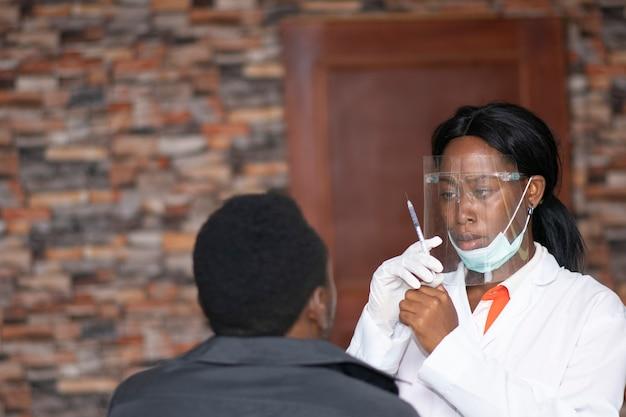 Dottoressa africana in procinto di vaccinare un giovane uomo