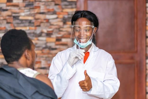 La dottoressa africana dà a un paziente un pollice in su dopo aver somministrato un'iniezione