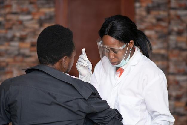 Medico africano femminile che dà a un paziente un concetto di vaccino contro il coronavirus