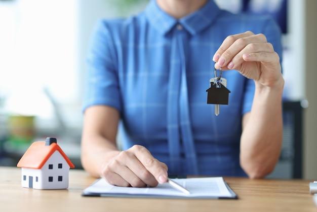 L'agente donna porge le chiavi di casa e la penna per firmare i documenti che acquistano il concetto di proprietà immobiliare