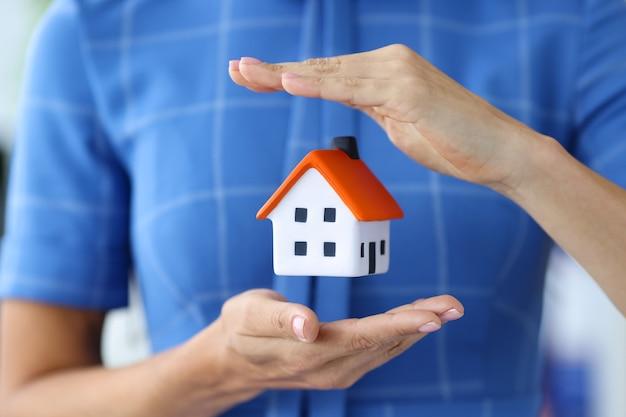 Agente immobiliare agente femminile che tiene il layout della casa che acquista immobili con il concetto di ipoteca