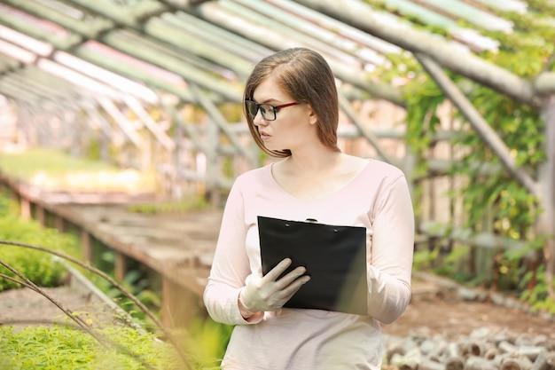 Ingegnere agricolo femminile che lavora in serra