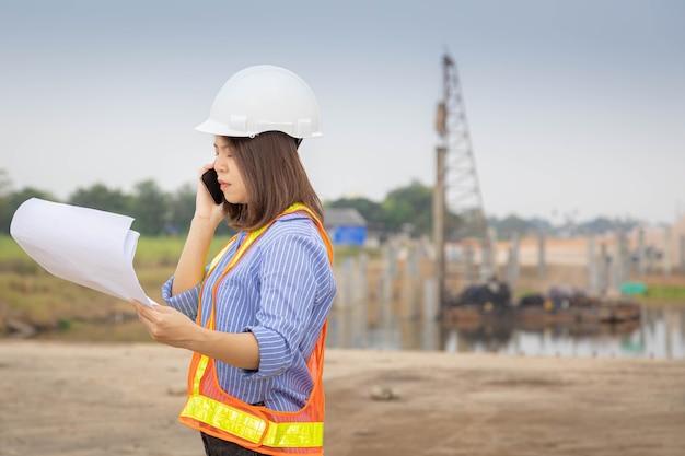 Un capo architetto donna che indossa un casco di sicurezza e un gilet arancione sta parlando del progetto al telefono in cantiere o in cantiere