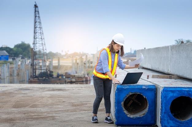 Capo architetto femminile che lavora con laptop e progetti in cantiere o in cantiere.