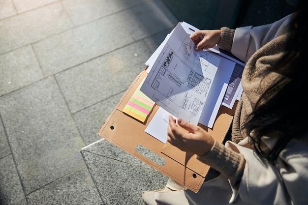 Architetto femminile che studia piano architettonico sulla strada