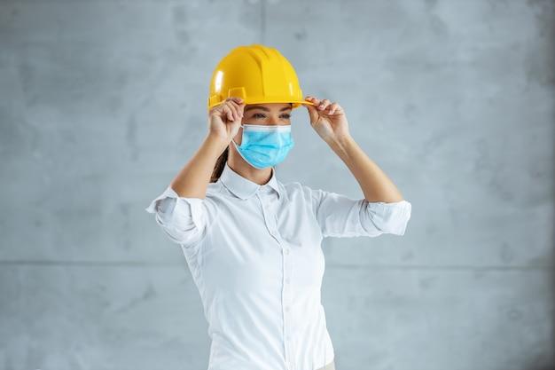 Architetto femminile con maschera facciale che mette il casco sulla testa e si prepara ad andare avanti ste.