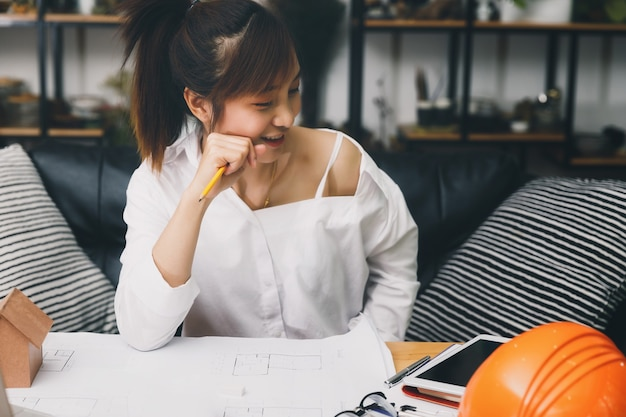 Architetto femminile che lavora al progetto degli architetti del modello in ufficio.