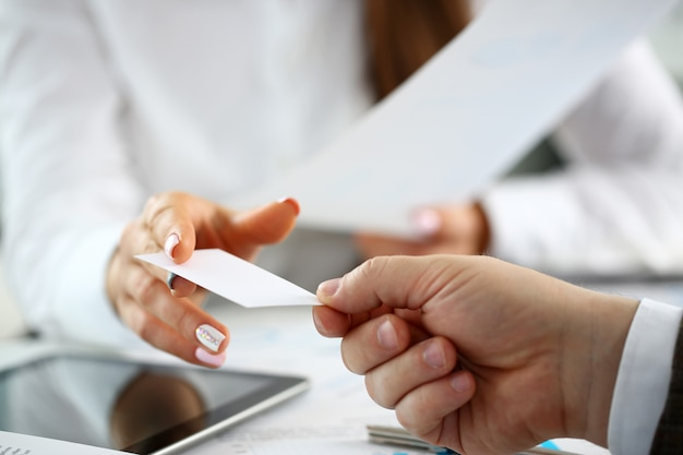 Braccio femminile in tuta dare biglietto da visita in bianco al visitatore