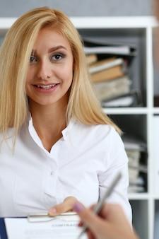Il braccio femminile in camicia bianca offre il modulo del contratto sul blocco degli appunti e sulla penna d'argento per firmare il primo piano.