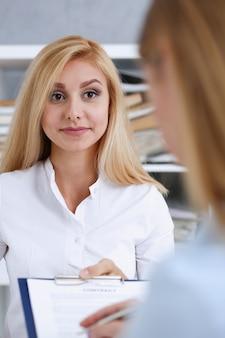 Braccio femminile in camicia bianca offre forma di contratto sul blocco appunti