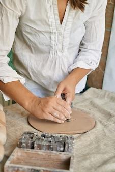 La ceramista artigiana fa un'impressione di lettere su uno strato di argilla