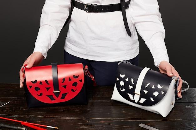 Artigiano femminile che dimostra eleganti borse in pelle fatte a mano