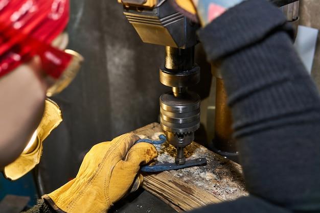 Artigiana che esegue la lavorazione di opere d'arte in metallo su una macchina di perforazione con fresa svasata, concentrarsi sul pezzo