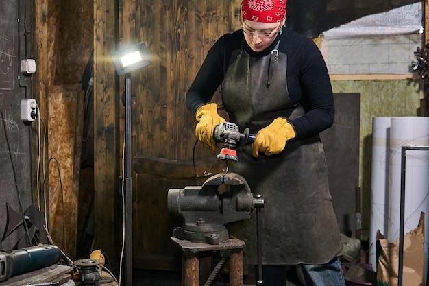 L'artigiano femminile gestisce un'opera d'arte in metallo serrata in una morsa con una smerigliatrice angolare in un'officina