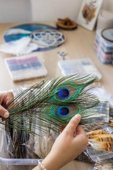 Artista femminile che sceglie piuma di pavone naturale per creare acchiappasogni all'amuleto dell'arredamento dell'officina