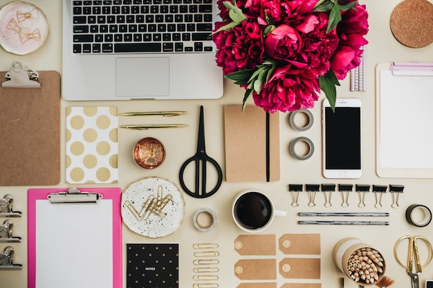 Area di lavoro artistica femminile con fiori di peonie rosa, laptop, telefono cellulare, appunti e accessori sulla superficie beige