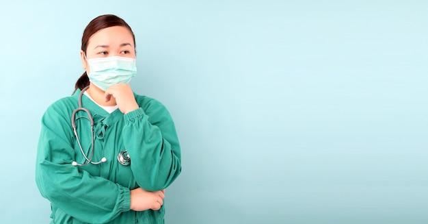 Femmina chirurgo asiatico, chirurgo sensazione di ansia, mostrando stetoscopio indossando maschera protettiva malattie infettive e coronavirus o covid-19, in studio con spazio di copia.