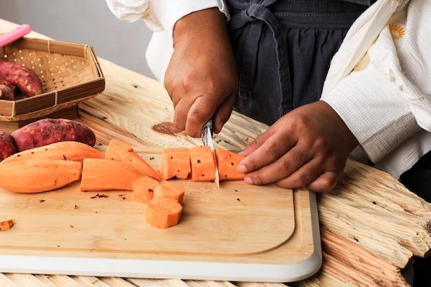 Femmina asiatica taglio a mano di patate dolci utilizzando un coltello su un tavolo di legno in cucina, processo che produce cibo tradizionale