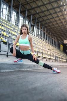 Atleta femminile che fa esercizi di stretching mattina allo stadio. concetto di sport per la vita in salute
