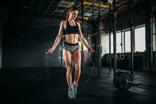 Atleta femminile esercizio con una corda per saltare in palestra sportiva. allenamento attivo della donna nel fitness club