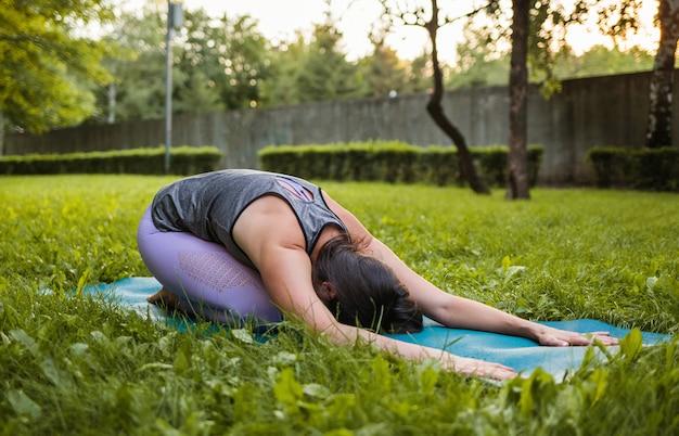 Un atleta femminile esegue una posa di yoga balasana al tramonto in un parco