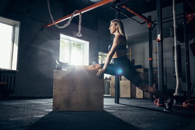 L'atleta femminile che si allena duramente nel fitness in palestra e nel concetto di vita sana