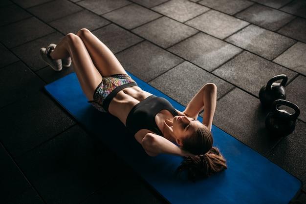 Atleta femminile treni premere in palestra sportiva, vista dall'alto. giovane donna nel fitness club, allenamento in forma