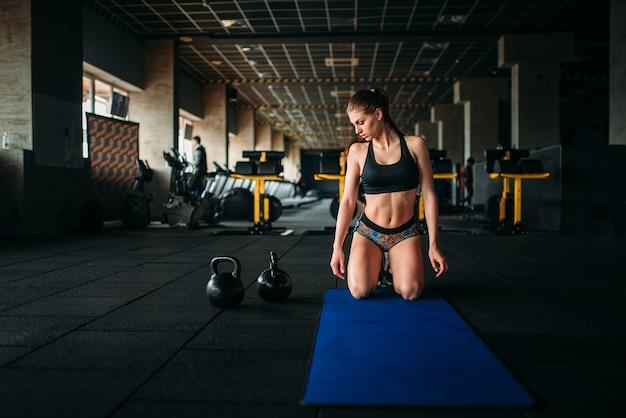 Atleta femminile treni premere in palestra sportiva, vista dall'alto