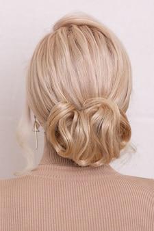 Parte posteriore femminile con capelli biondi e acconciatura di moda nel salone di bellezza