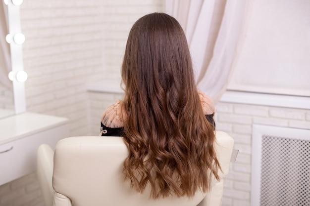Parte posteriore femminile con capelli lunghi, ricci, castani, nel salone di parrucchiere