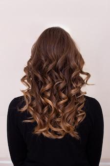 Dorso femminile con capelli lunghi, ricci, ombre, castani