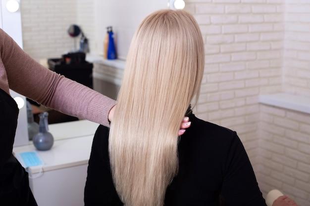 Parte posteriore femminile con capelli biondi lunghi dritti nel salone di parrucchiere