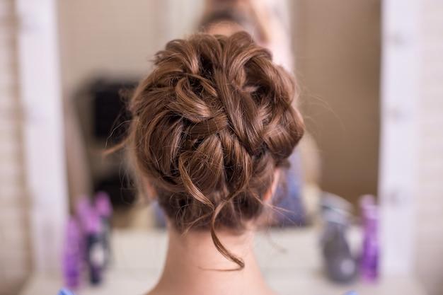 Parte posteriore femminile con acconciatura da sposa romantica nel salone di parrucchiere