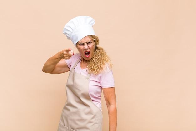Panettiere femminile che indica alla macchina fotografica con un'espressione aggressiva arrabbiata