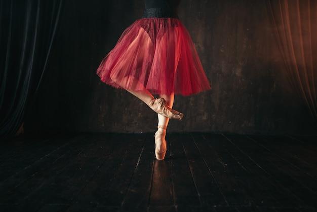 Piedini femminili del ballerino di balletto in pointes. ballerina in abito rosso e pratica nera ballando sul palco del teatro