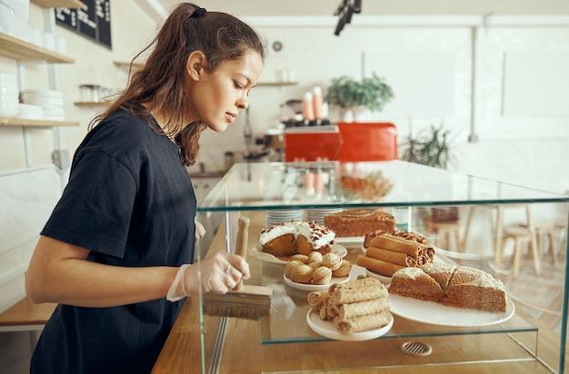 Barista femminile in vetrina con dessert nella caffetteria. giovane operaio di pasticceria e caffetteria.