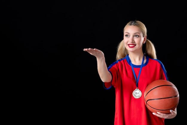 Giocatore di basket femminile con palla e medaglia d'oro su sfondo nero trofeo atleta