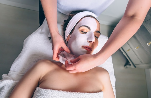 Estetista femminile che rimuove la maschera facciale di argilla alla giovane donna sdraiata con gli occhi chiusi nella spa. medicina, sanità e concetto di bellezza.