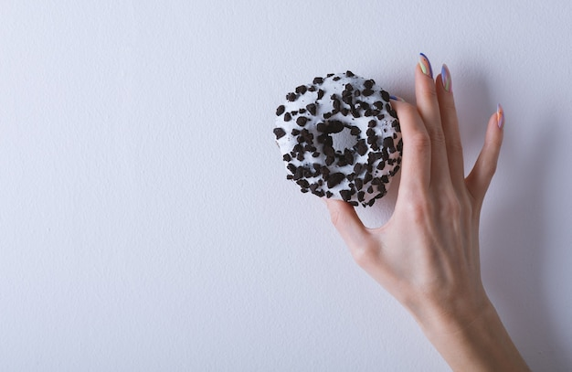 La bella mano femminile con il manicure tiene una ciambella