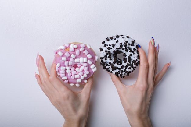 Belle mani femminili con manicure alla moda che tiene le ciambelle